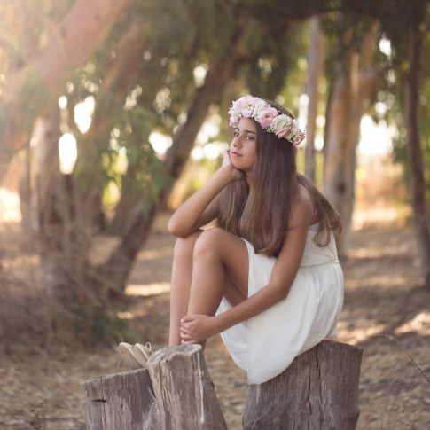 בוק בת מצווה של יובל שיושבת על גזע עץ