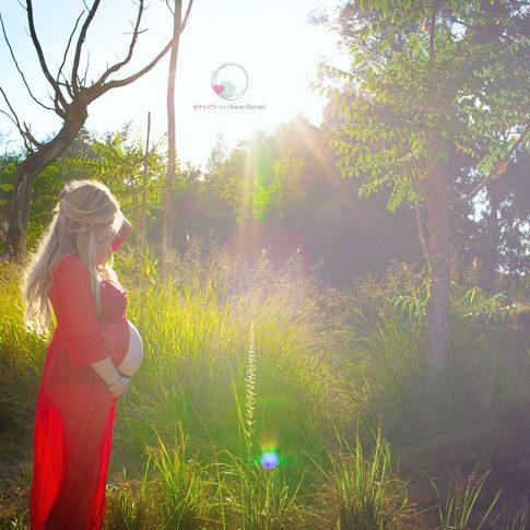 צילום הריון בטבע בשמלה אדומה